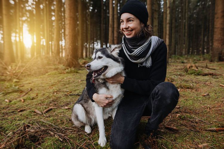 Young woman with dog in the forest