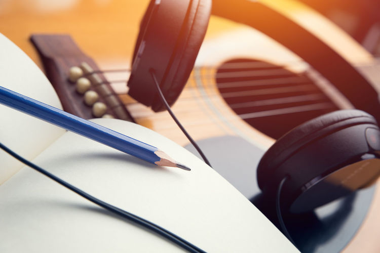 Close-up of pencil and headphones with guitar
