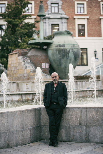 Portrait of bald businessman with hands in pockets standing against fountain in city