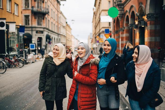 Happy multi-ethnic muslim female friends standing on street in city