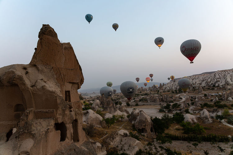 Hot air balloons flying over rocks