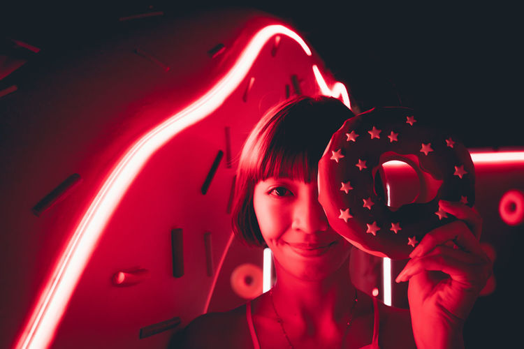 Portrait of young woman holding artificial donut against illuminated red neon light in darkroom