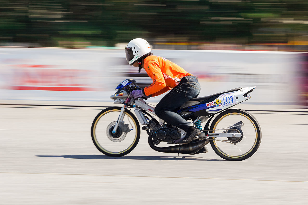 blurred motion, motion, helmet, speed, transportation, headwear, riding, ride, mode of transportation, sport, real people, side view, full length, on the move, land vehicle, men, sports helmet, one person, sports clothing, competition, skill, crash helmet, outdoors