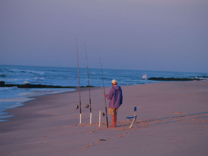 Rear view of man with fishing rod standing on beach at sunset