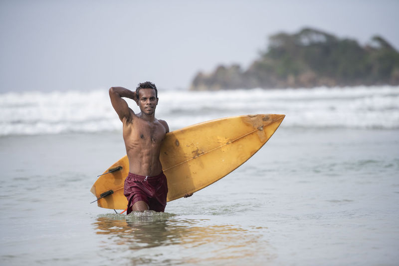 Portrait of shirtless man with surfboard wading in sea against sky