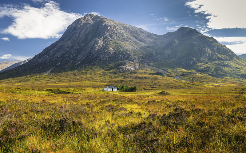 The remote Lagangarbh Hut in front of Buachaille Etive Mor in Glen Coe on a beautiful summer afternoon, Scotland Glencoe Scotland Beauty In Nature Cloud - Sky Day Environment Field Grass Highlands Landscape Mountain Mountain Peak Mountain Range Nature No People Outdoors Scenics - Nature Scottish Highlands Sky Tranquil Scene