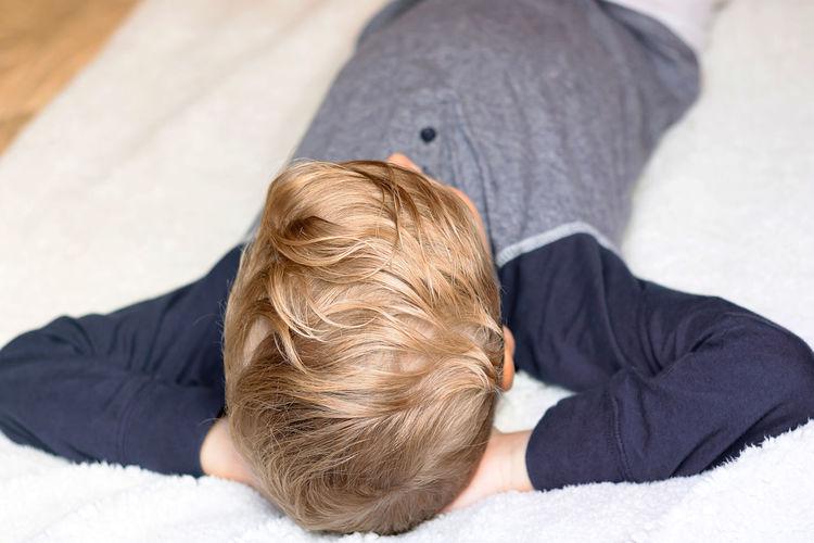 Rear view of boy lying on sofa