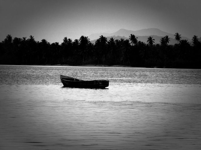 Small boat abandoned in a tropical bay rendered in black and white Water Nautical Vessel Tree Waterfront Beauty In Nature Mode Of Transportation Plant Tranquility Transportation Scenics - Nature Sky Tranquil Scene Nature No People Silhouette Lake Outdoors Day Non-urban Scene Rowboat Anchored