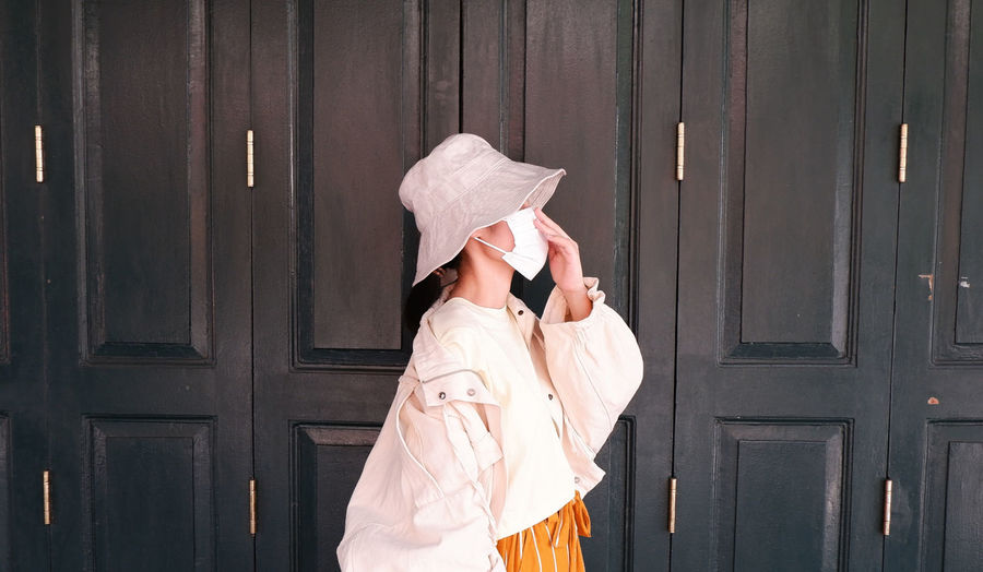 Side profile of an asian woman portrait, wearing a white mask and a sun hat