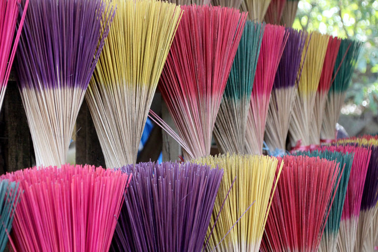 Close-up of multi colored brooms for sale at market