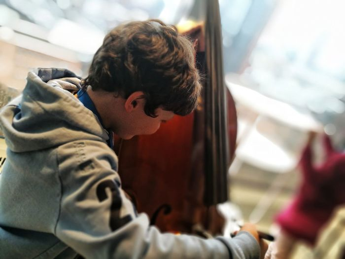 Side view of boy playing double bass