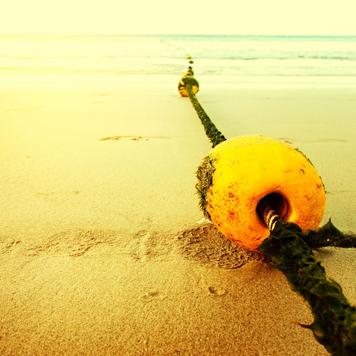 Close-up of yellow umbrella on beach against sky