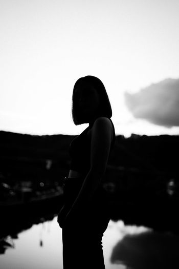 Side view of silhouette woman standing on mountain against sky