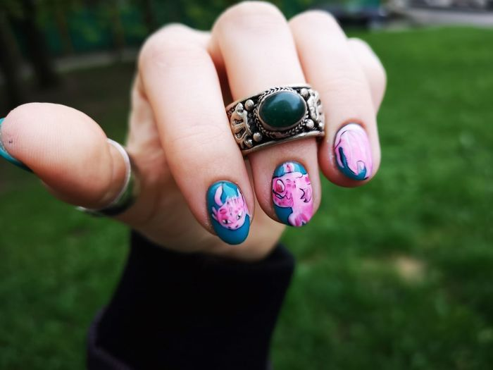 Close-Up Of Woman Hand Wearing Nail Polish And Finger Ring Outdoors