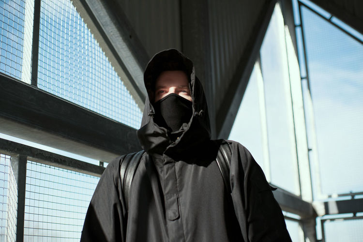 Thoughtful man wearing mask and hooded shirt standing by metallic grate