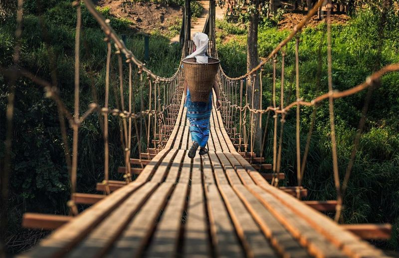 Rear View Full Length Of Woman Carrying Basket On Rope Bridge