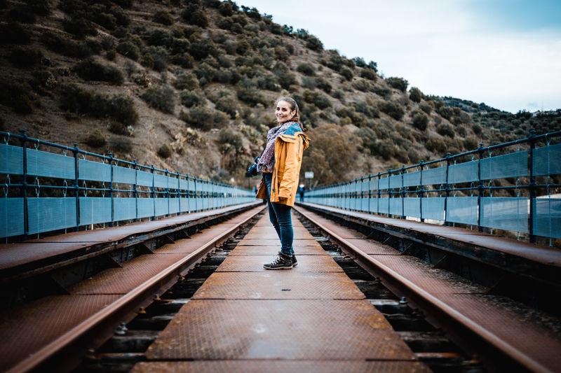 Portrait of young woman standing on railway bridge