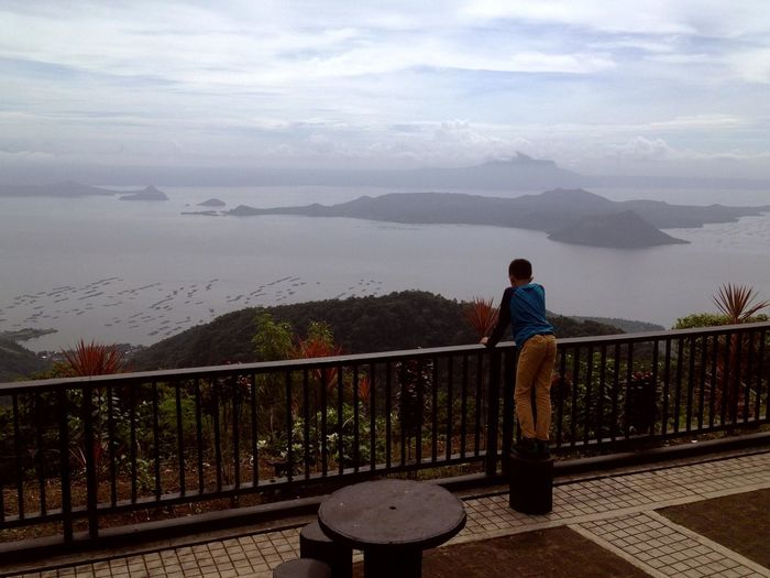 Beauty In Nature Day Discovery Full Length Lake Leisure Activity Men Mountain Nature One Man Only One Person Outdoors People Railing Rear View Scenics Sky Standing Taal Lake Taal Volcano Tagaytay Water Young Adult
