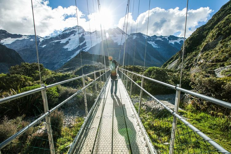 Rear view of woman on footbridge against mountains