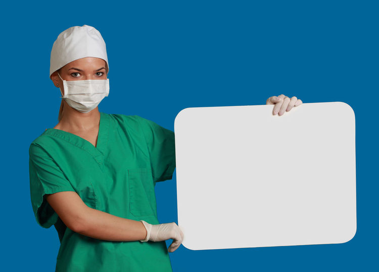 Young woman doctor keeping a white board, against a blue background. Copy Space Doctor  Healthcare Medicine Nurse White Board Adults Only Blue Blue Background Green Color Healthcare And Medicine Keeping Looking At Camera Medical Cannabis Message One Person People Physician Placard Studio Shot Surgeon Surgical Cap Surgical Mask Young Adult
