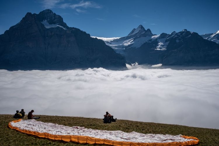 People sitting on field by cloudscape against mountains