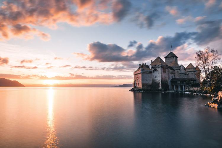 Historic Chateau de Chillon at Sunset. Castle Chateau De Chillon Geneve, Switzerland Architecture Beauty In Nature Building Building Exterior Built Structure Cloud - Sky Idyllic Lake Geneva Nature No People Orange Color Outdoors Reflection Scenics - Nature Sea Sky Sunset Tranquility Water Waterfront