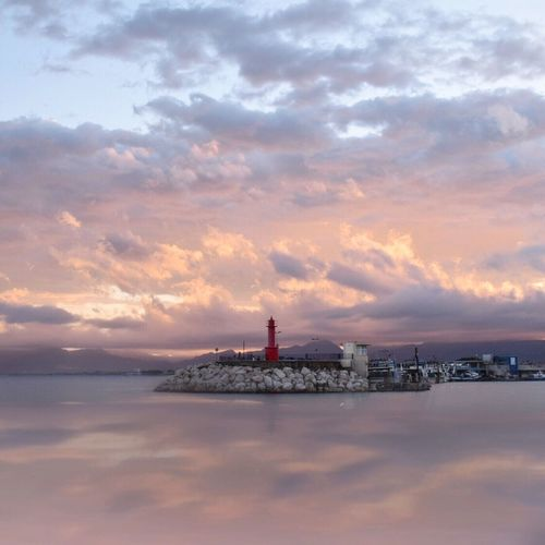 Quiet afternoon Sea And Sky Sea Calm Salmon Colored Colourful Clouds Red Sky Lighthouse Sunset Cambrils
