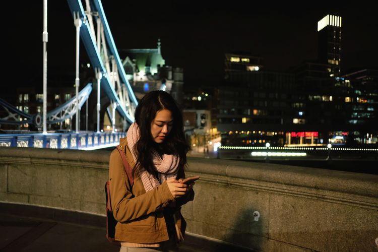 Woman standing on bridge in city at night