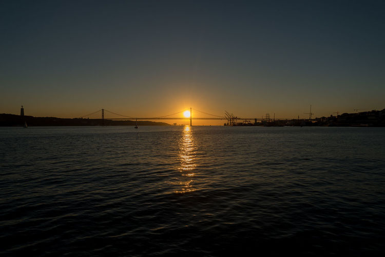 Sunset over Cristo Rei and 25th April Bridge in the Lisboa Bay, Lisbon - Portugal Portugal Sunset Silhouettes Sunset_collection Architecture Beauty In Nature Bridge Built Structure Connection Lisbon Nature No People Outdoors Reflection Scenics - Nature Sea Silhouette Sky Sun Sunset Tourism Tranquil Scene Tranquility Transportation Water Waterfront