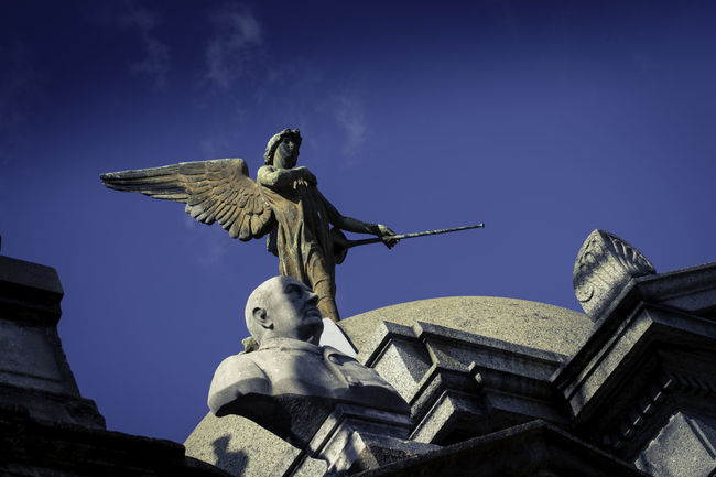La Recoleta Cemetery, Buenos Aires, Argentina Upper class death in Argentina. The myriad of tombs and mausaleums open to the public housing the wealthy and famous of Argentine society. A macabre place of death and celebration. The Photojournalist - 2018 EyeEm Awards Angel Animal Wildlife Architecture Art And Craft Bird Built Structure Clear Sky Creativity Day Flying Human Representation Low Angle View Nature No People Representation Sculpture Sky Statue Vertebrate
