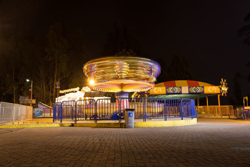 Illuminated Night Amusement Park Amusement Park Ride Arts Culture And Entertainment Architecture Motion Built Structure Blurred Motion Building Exterior City Long Exposure Sky Spinning Carousel Lighting Equipment Street Ferris Wheel No People Outdoors Light Merry-go-round Capture Tomorrow