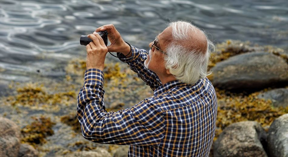 A tourist Senior Adult One Person Water Nature Sea Outdoors Day Beach Gray Hair One Animal One Senior Man Only Animal Themes Real People Standing Adult One Man Only Adults Only Only Men Beauty In Nature People