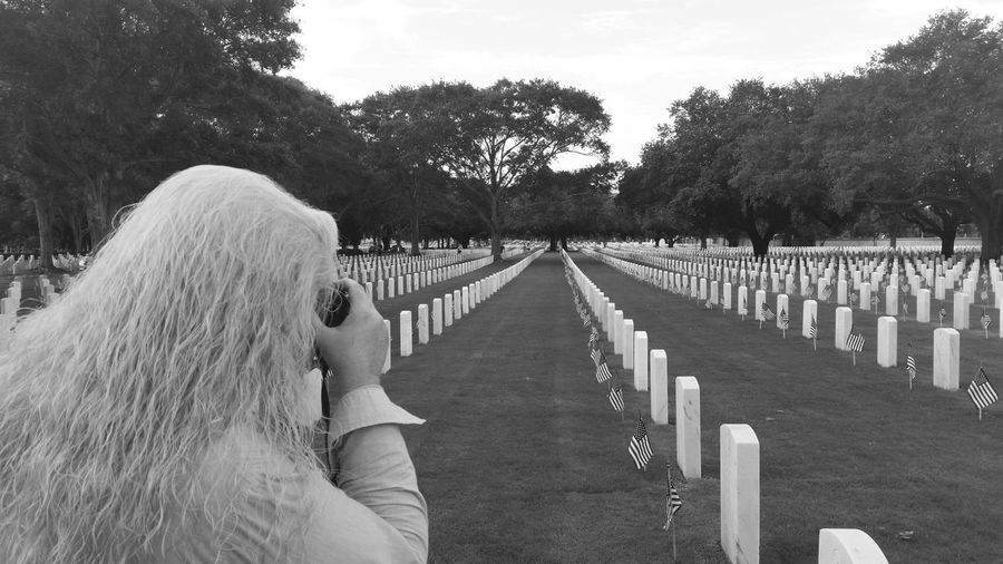Rear View Of Woman Photographing At Cemetery