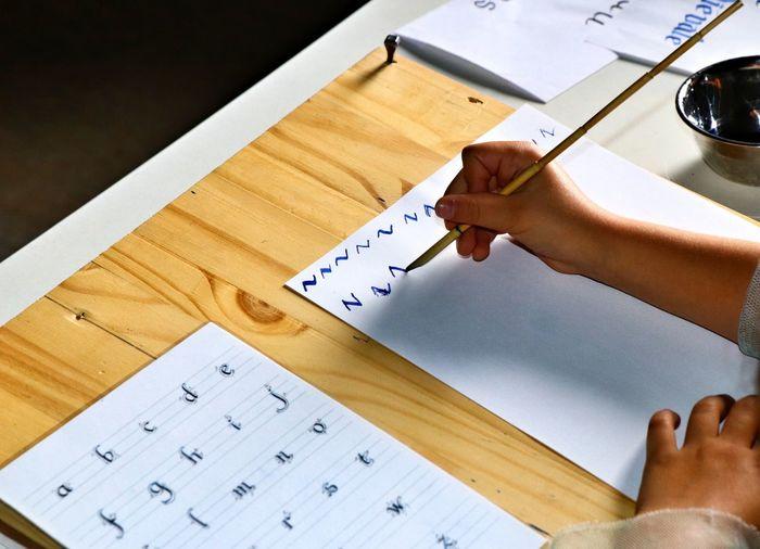 High angle view of hand  doing caligraphy
