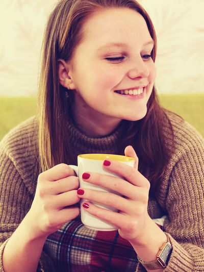 Portrait of a young woman drinking coffee cup