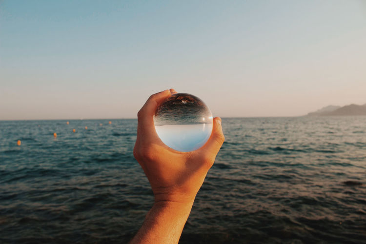 Cropped hand holding crystal ball against sea and sky during sunset