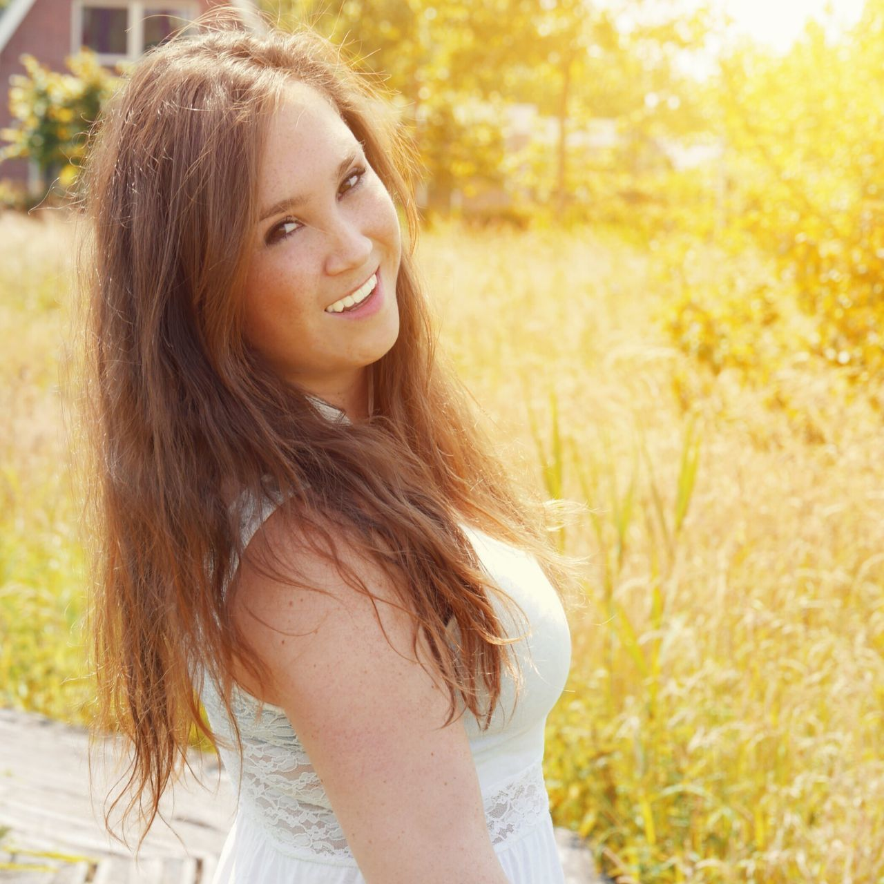 long hair, one person, smiling, young adult, real people, outdoors, beautiful woman, portrait, looking at camera, happiness, young women, nature, field, sunlight, standing, day, grass