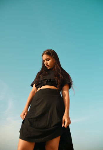 Low angle view of woman in black dress standing against clear sky