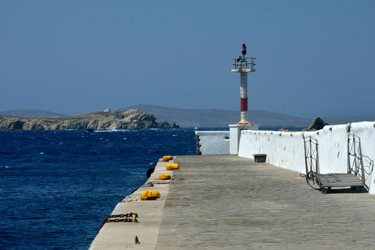 seaview of a pier in Mykonos with light equipment and moorings Sky Water Sea Guidance Built Structure Lighthouse Direction Mountain Tower Architecture Safety Nature Security Day Clear Sky Building Exterior No People Protection Blue Outdoors Navigation Light Light Equipment Nautical Equipment Pier Seascape Mykonos,Greece Port Dock Panorama Maritime Photography Panoramic View Nature
