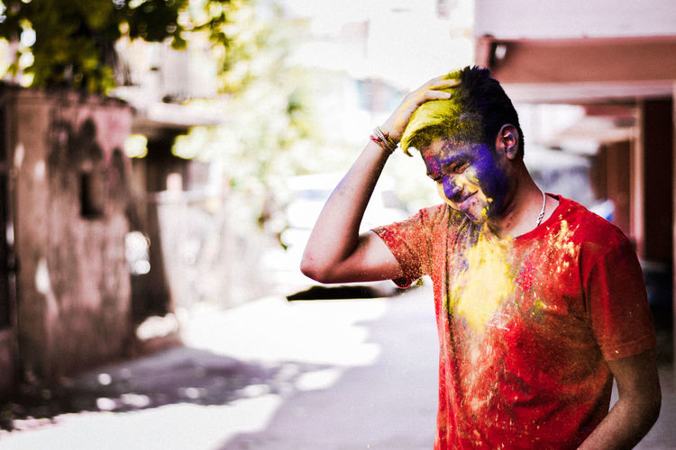 Happy boy covered with holi color standing on road