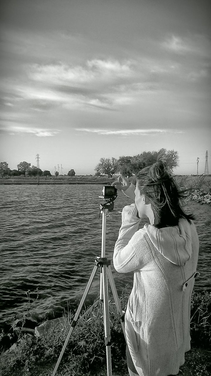 water, rear view, photography themes, technology, photographing, river, real people, leisure activity, camera - photographic equipment, day, outdoors, sky, standing, women, men, nature, one person, digital single-lens reflex camera, adult, people, adults only