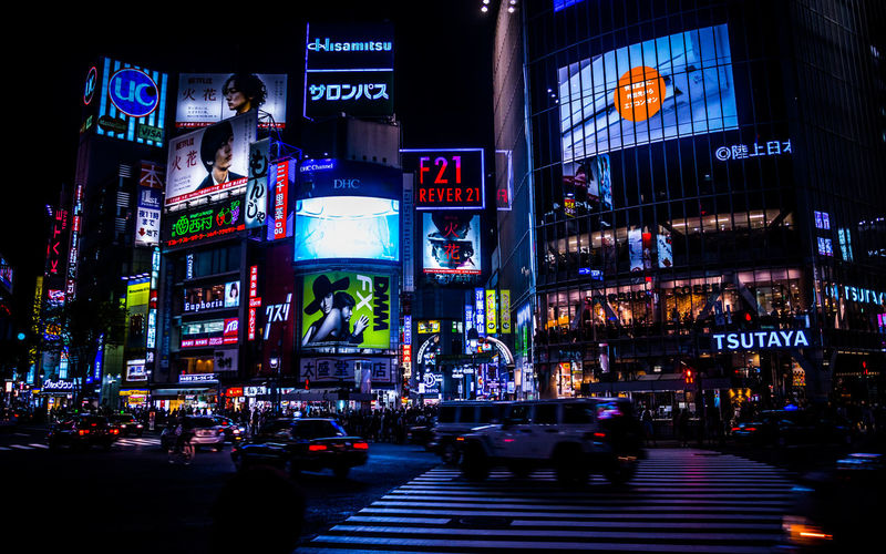 Vehicles On Street Against Illuminated Billboards On Buildings In Shibuya