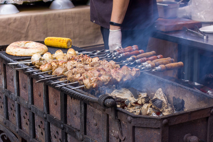 Midsection of man standing by barbecue grill at market stall