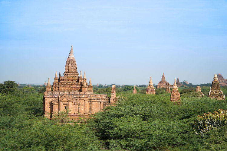 Panoramic view of pagodas in green fields in bagan