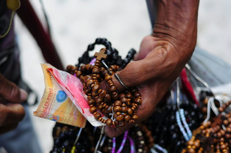 Close-up of vendor with money and rosaries