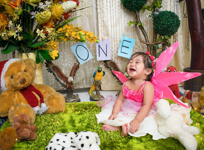 Cheerful Shirtless Baby Girl Sitting Amidst Stuffed Toys During Birthday