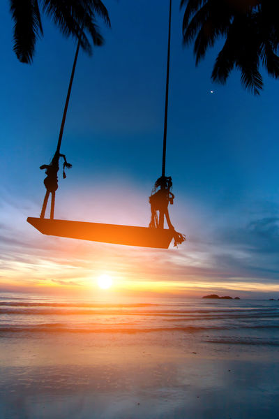 Beach Beauty In Nature Fun Horizon Over Water Land Leisure Activity Lifestyles Men Nature Orange Color Outdoors People Real People Scenics - Nature Sea Silhouette Sky Sunset Swing Tree Water