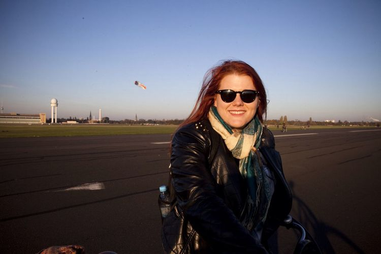 Portrait Of Smiling Woman At Tempelhof Airport Against Clear Blue Sky