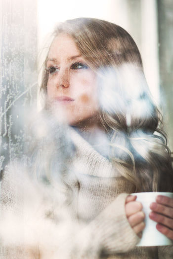 Adult Beautiful Woman Close-up Coffee - Drink Coffee Cup Day Drink Drinking Freshness Lifestyles Looking Through Window One Person One Young Woman Only People Real People Warm Clothing Window Winter Women Young Adult Young Women