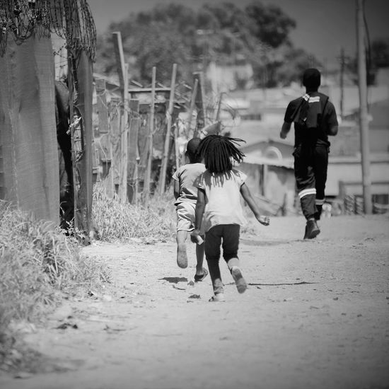 Child Adult Childhood People Outdoors Girls Boys Two People Togetherness Kids Being Kids Kids Playing Kids Running Kids At Play Youngsters Walking Away Township Ghetto Slums Poverty Poor